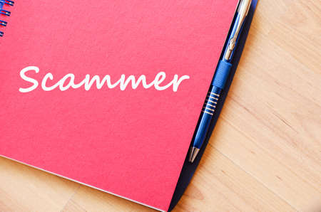 Scammer text concept write on notebook with pen