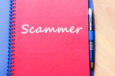 scammer: Scammer text concept write on notebook with pen