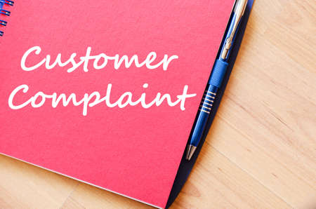complaint: Customer complaint text concept write on notebook with pen