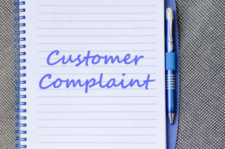 grievance: Customer complaint text concept write on notebook with pen