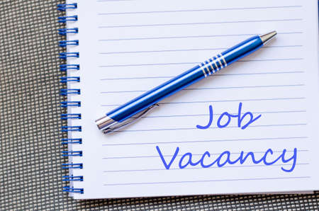 vacancy: Job vacancy text concept write on notebook with pen