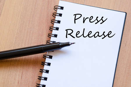 Press release text concept write on notebook with pen Stock Photo