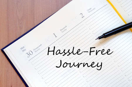 hassle: Hassle free journey text concept write on notebook with pen Stock Photo
