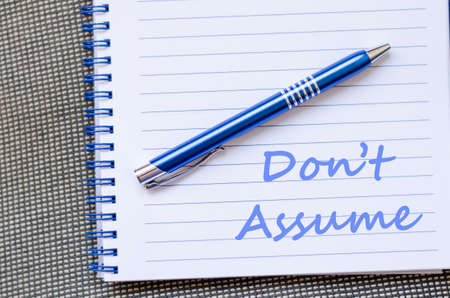 speculating: Dont assume text concept write on notebook with pen