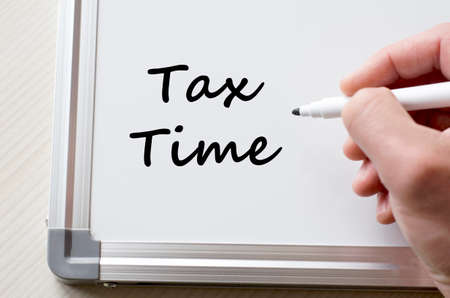 government services: Human hand writing taxtime on whiteboard Stock Photo