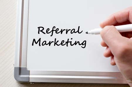 referral marketing: Human hand writing referral marketing on whiteboard