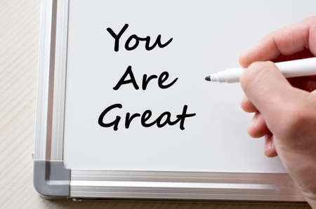 flattery: Human hand writing you are great on whiteboard Stock Photo