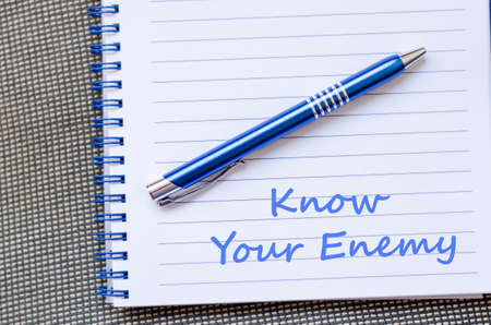 enemy: Know your enemy text concept write on notebook with pen