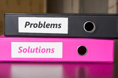 idea hurdle: Bright office folders over dark background and problems and solutions text concept