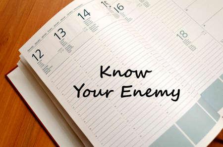 competitividad: Conoce a tu enemigo concepto de texto escribir en el cuaderno