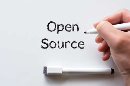 human source: Human hand writing open source on whiteboard