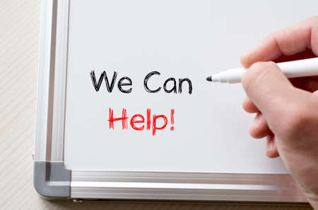 can we help: Human hand writing we can help on whiteboard Stock Photo