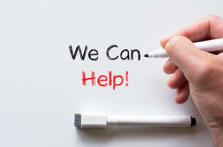 Human hand writing we can help on whiteboard Stock Photo
