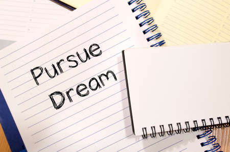 pursue: Pursue dream text concept write on notebook Stock Photo