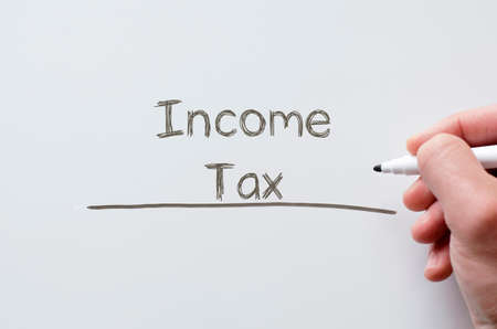 income tax: Human hand writing income tax on whiteboard