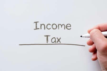 Human hand writing income tax on whiteboard