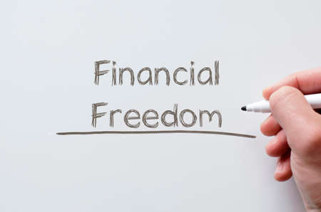 frugal: Human hand writing financial freedom on whiteboard