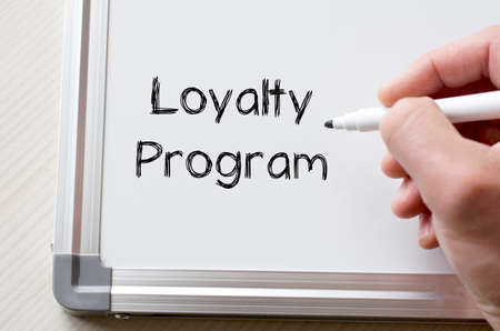 frequent: Human hand writing loyalty program on whiteboard