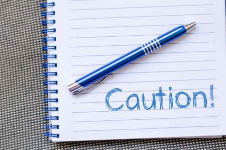 Caution text concept write on notebook Stock Photo