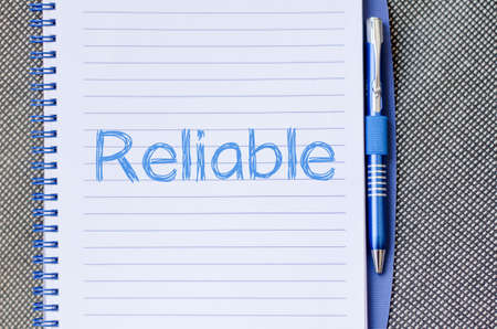 reliable: Reliable text concept write on notebook Stock Photo