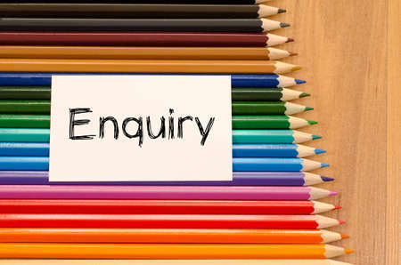 Enquiry text concept and colored pencil on wooden background