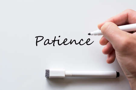 yielding: Human hand writing patience on whiteboard
