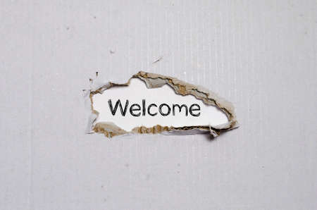 appearing: The word welcome appearing behind torn paper. Stock Photo
