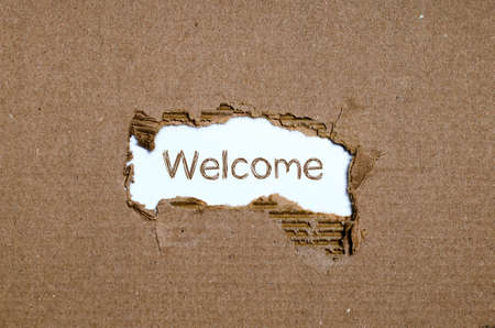 usher: The word welcome appearing behind torn paper. Stock Photo