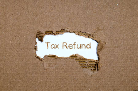 repay: The word tax refund appearing behind torn paper. Stock Photo