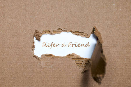 affiliation: The word refer a friend appearing behind torn paper. Stock Photo