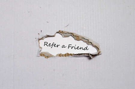 appearing: The word refer a friend appearing behind torn paper. Stock Photo