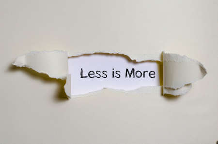pragmatic: The word less is more appearing behind torn paper. Stock Photo