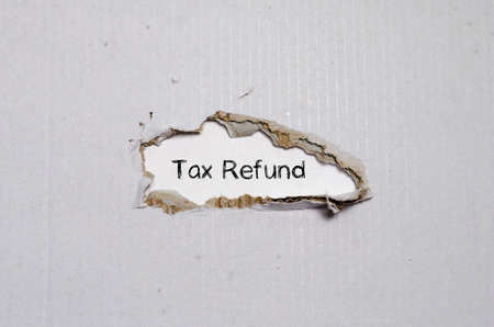 refund: The word tax refund appearing behind torn paper. Stock Photo