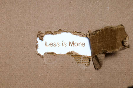 simplification: The word less is more appearing behind torn paper. Stock Photo
