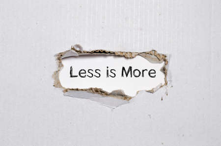 less: The word less is more appearing behind torn paper. Stock Photo