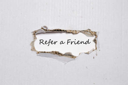 refer: The word refer a friend appearing behind torn paper. Stock Photo