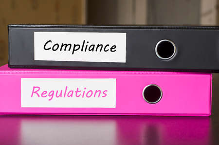 compliant: Bright office folders over dark background and compliance regulations text concept Stock Photo
