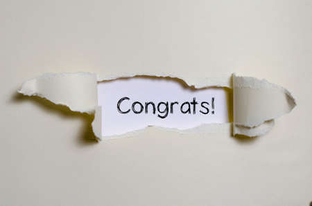 appearing: The word congrats appearing behind torn paper. Stock Photo
