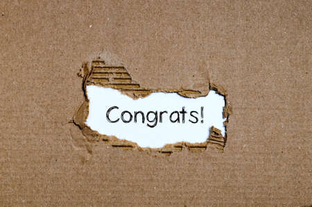 The word congrats appearing behind torn paper. Stock Photo