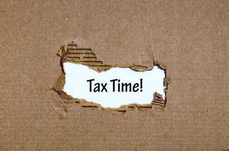 taxpayer: The word tax time appearing behind torn paper Stock Photo