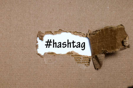appearing: The word hashtag appearing behind torn paper