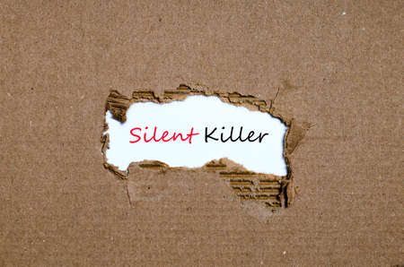 appearing: The word silent killer appearing behind torn paper Stock Photo