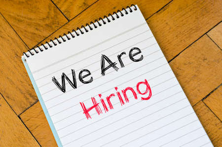 new recruit: We are hiring text concept on notebook over wooden background
