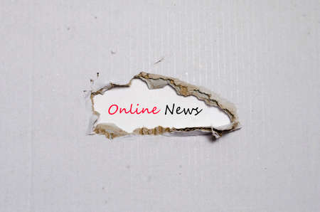urgent announcement: The word online news appearing behind torn paper