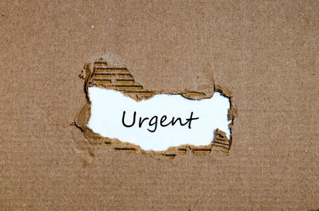 justify: The word urgent appearing behind torn paper Stock Photo