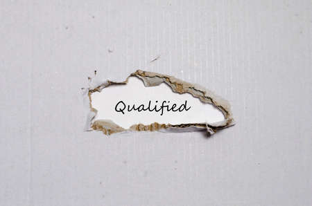 achivement: The word qualified appearing behind torn paper Stock Photo