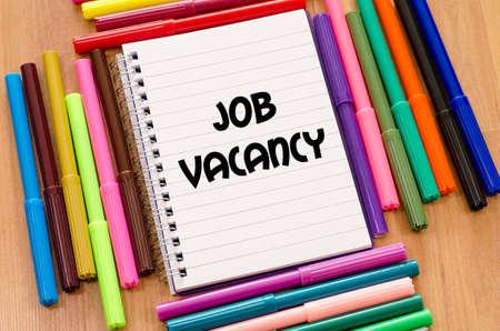 vacancy: Job vacancy written on notebook over wooden background
