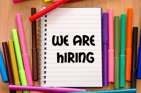 new recruit: We are hiring written on notebook over wooden background