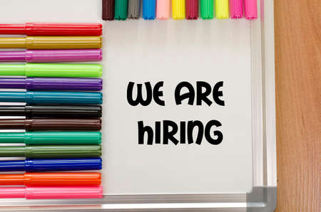 recruit help: We are hiring written on whiteboard over wooden background