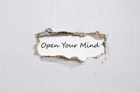 receptive: The word open your mind appearing behind torn paper